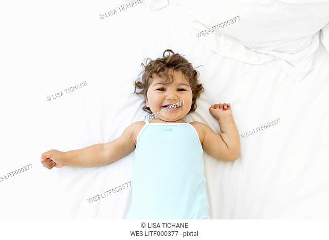 Portrait of happy baby girl lying on a white bed