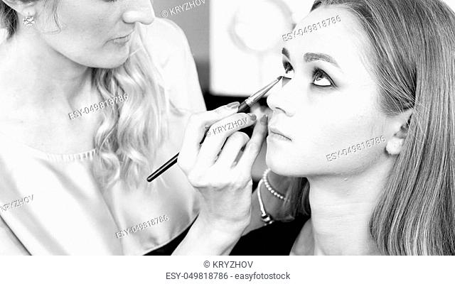 Closeup photo of makeup artist painting model' s eyes with brush