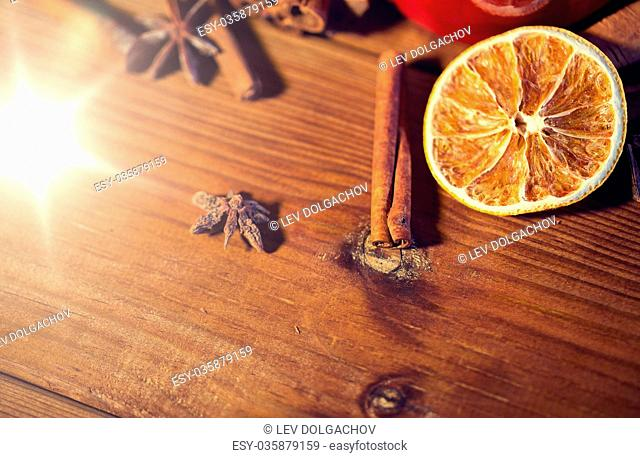 christmas, holidays, cooking and spice concept - close up of cinnamon, anise and dried orange on wooden board