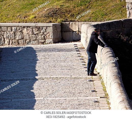 Man on bridge over Adaja river, Ávila, Spain