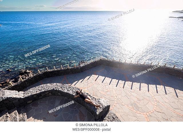 Spain, Tenerife, Woman sunbathing on wall near sea
