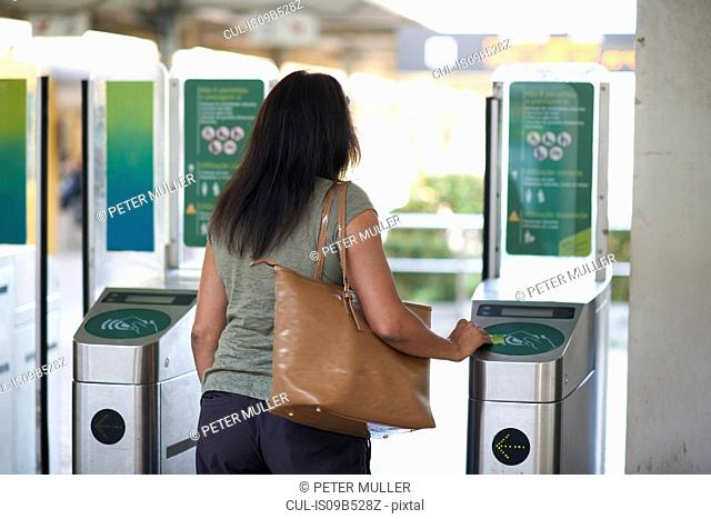 Rear view of woman using ticket touchscreen at railway ticket barrier