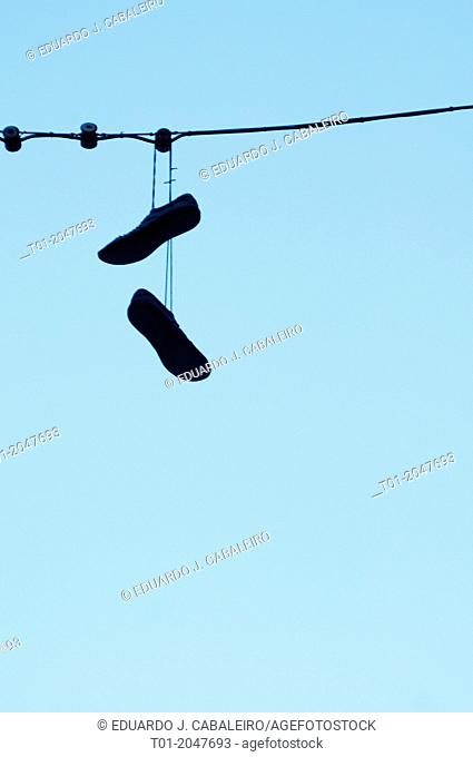 Silhouette of shoes hanging from a cable. Seville, Andalusia, Spain
