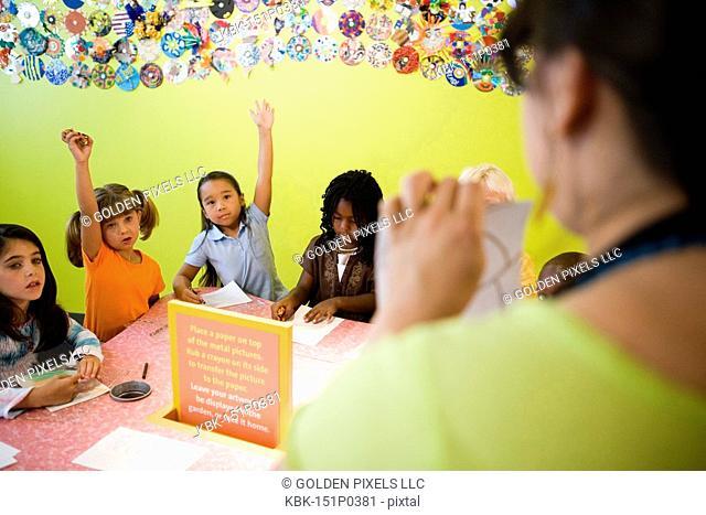 An art teacher demonstrating an art project to her young students in art class