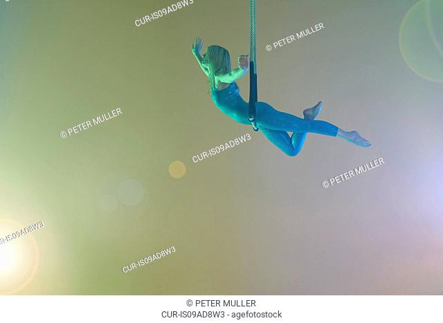 Trapeze artist balancing on trapeze
