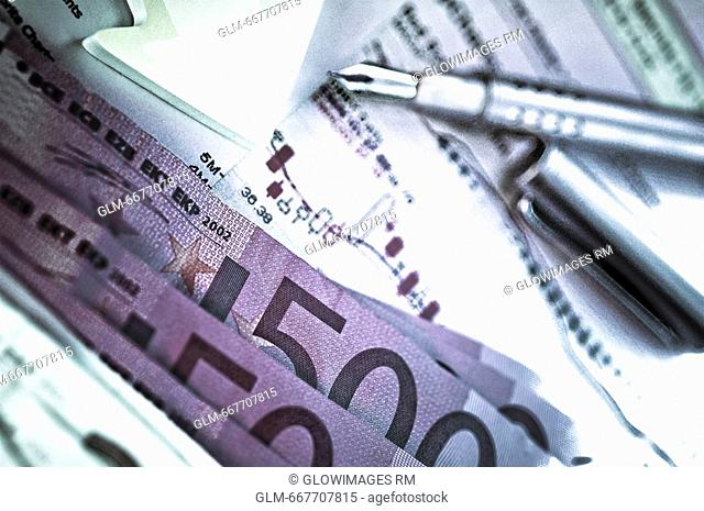 Close-up of five hundred euro banknotes and a pen on a sheet of paper