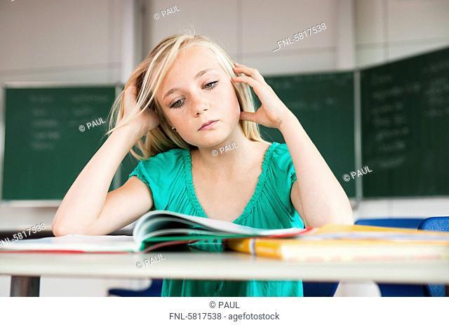Teenage girl in classroom thinking