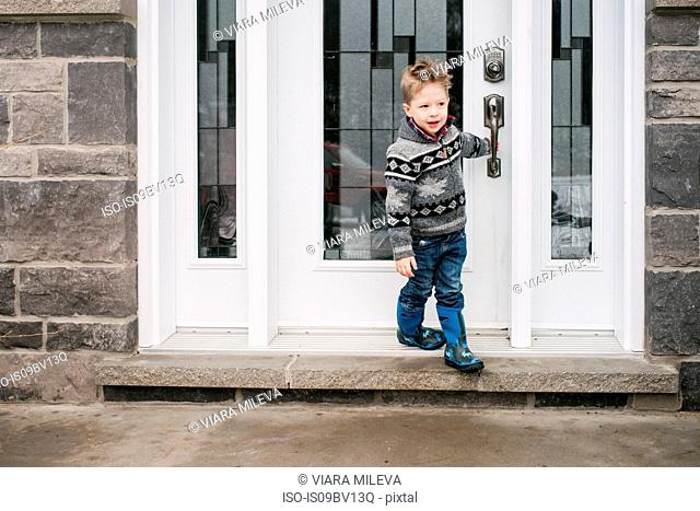 Boy closing door to leave house