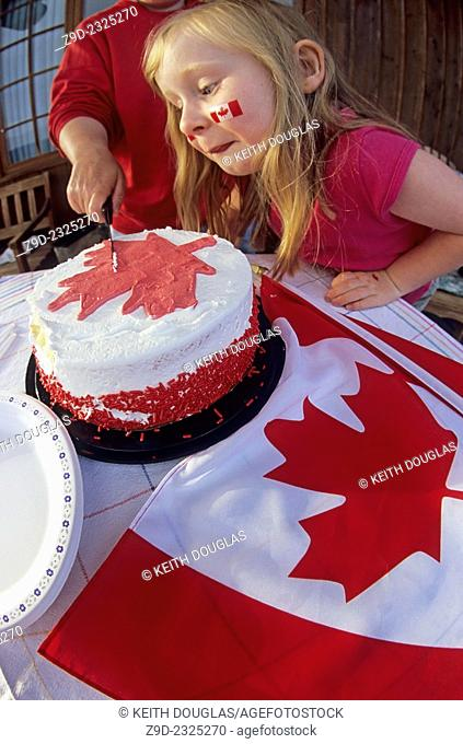Family celebrating Canada Day holiday with cake and flags