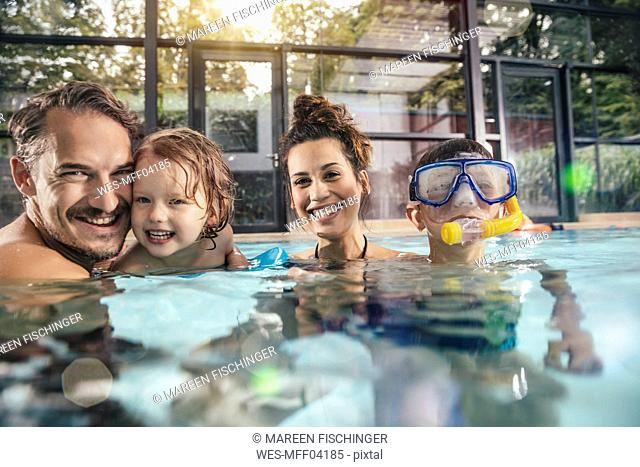 Portrait of happy family with two children in indoor swimming pool
