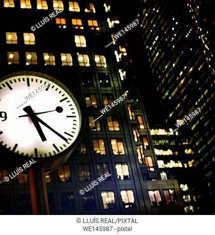 Primer plano de reloj y edificios de oficinas al fondo en Canada Squares, Canary Warf, London, England, UK, Closeup of clock and office buildings in the...
