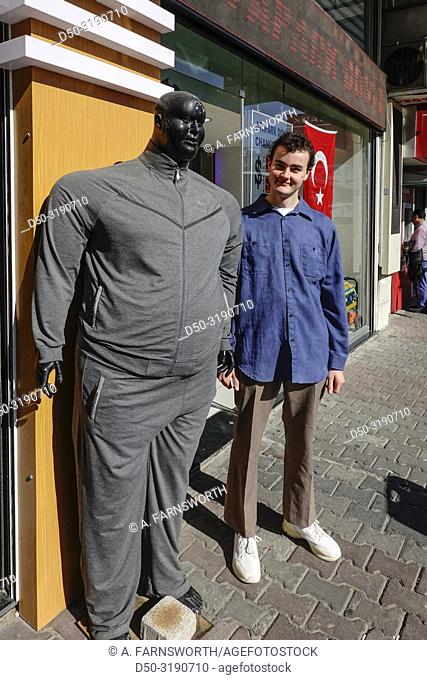 Istanbul, Turkey An 18 year old Swedish tourist stands next to an oversized mannequin on a busy shopping street