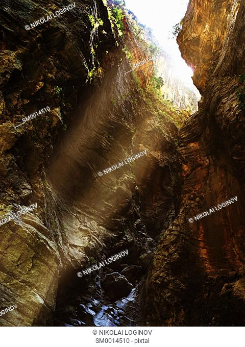 Vertical vivid greece canyon with ray of light dramatic landscape background backdrop