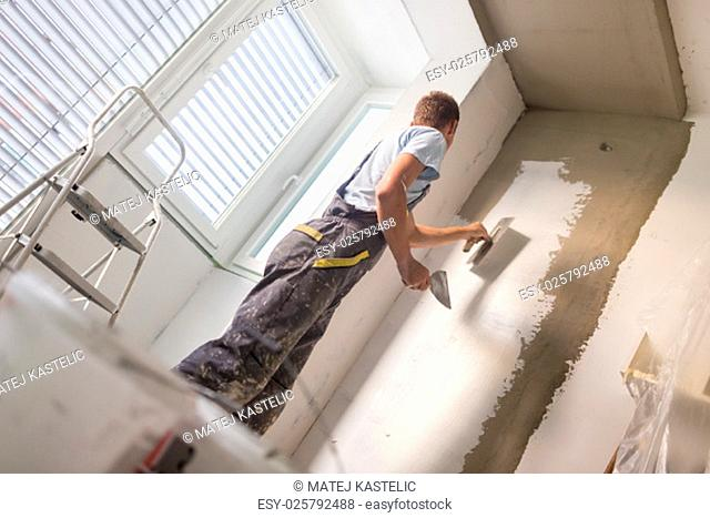 Thirty years old manual worker with wall plastering tools inside a house. Plasterer renovating indoor walls and ceilings with float and plaster