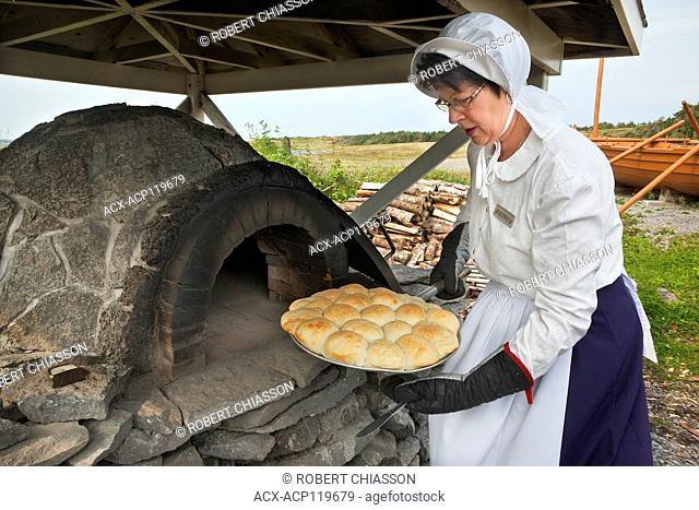 Parks Canada interpreter in period costume removing freshly baked bread from a traditional, outdoor brick and stone oven