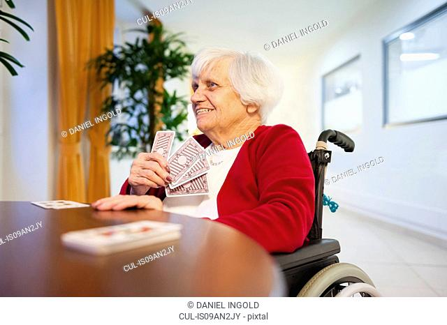 Senior woman in wheelchair playing card game at table