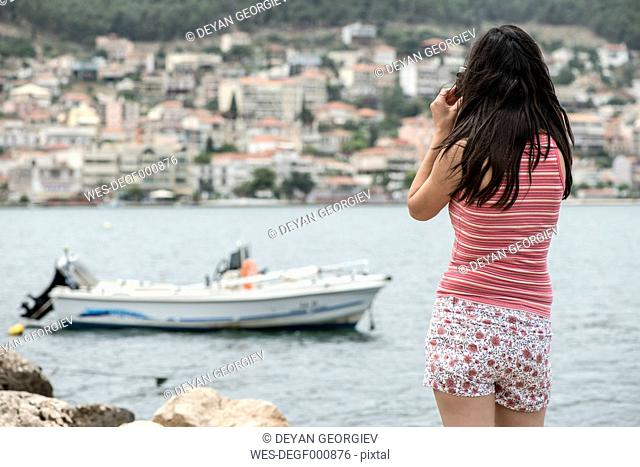 Greece, Amfilochia, woman taking picture at the sea