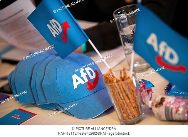 24 November 2018, Bavaria, Greding: Flags and caps with the AfD logo are lying on a table at the AfD Bavaria state party conference