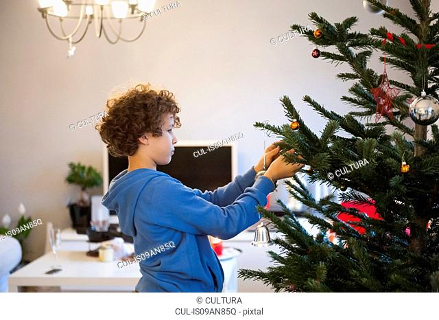 Boy hanging decorations on Christmas tree
