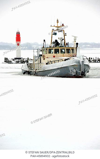 A ship sails in a wintery landscape before Ruegen island (background) in the iced harbor of Stralsund, Germany, 29 January 2014