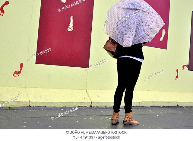Young woman looking at Berlin's East Side Gallery street art