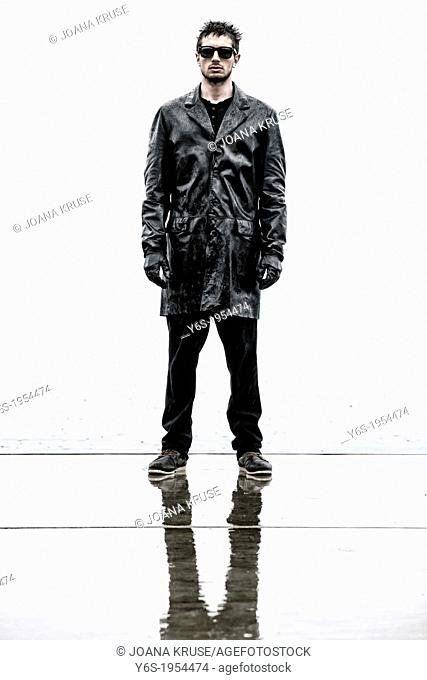 a sinister man in a black, wet leather jacket during rain