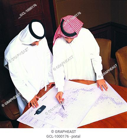 Arab businessmen discussing architectural sketches