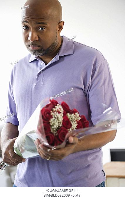 Sad African American man holding bouquet of roses