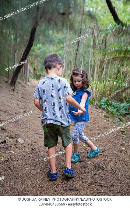 Brother and sister having fun on the Hauula Loop Trail while hiking in Oahu Hawaii