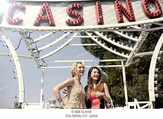 Two women standing in front of fairground ride, laughing