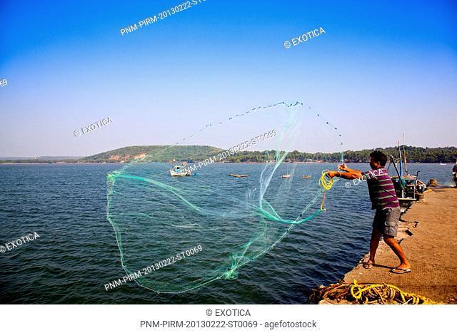 Fisherman throwing a fishing net in the sea, Chapora Harbour, Chapora, Bardez, North Goa, Goa, India