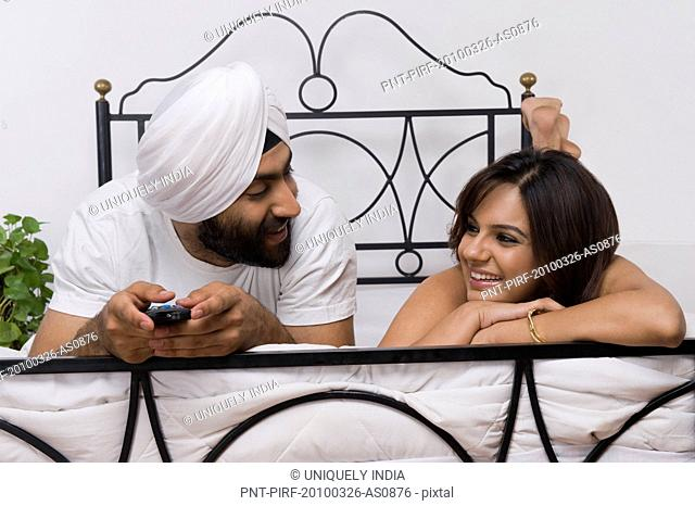 Sikh couple lying on the bed and looking at each other