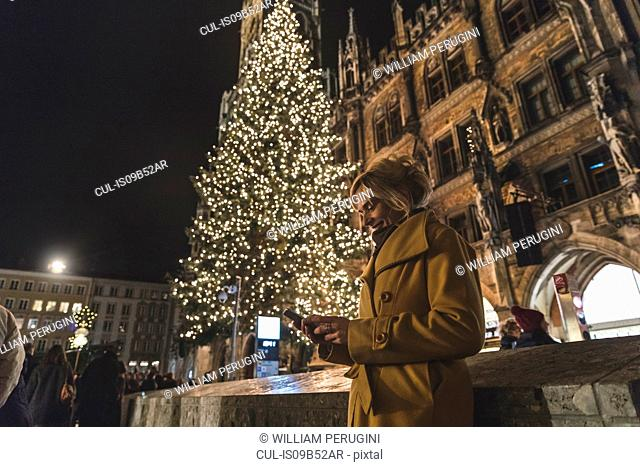 Woman looking at smartphone by christmas tree at night, Munich, Germany