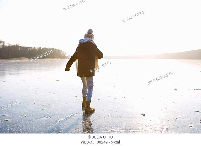 Germany, Brandenburg, Lake Straussee, back view of a girl walking on frozen lake