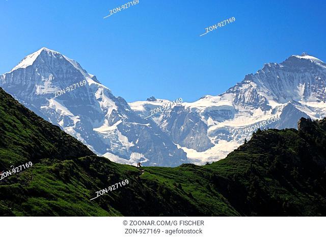 Blick über einen Bergsattel auf das Jungfrau-Joch zwischen Mönch, links, und Jungfrau, rechts, bei Grindelwald, Berner Oberland