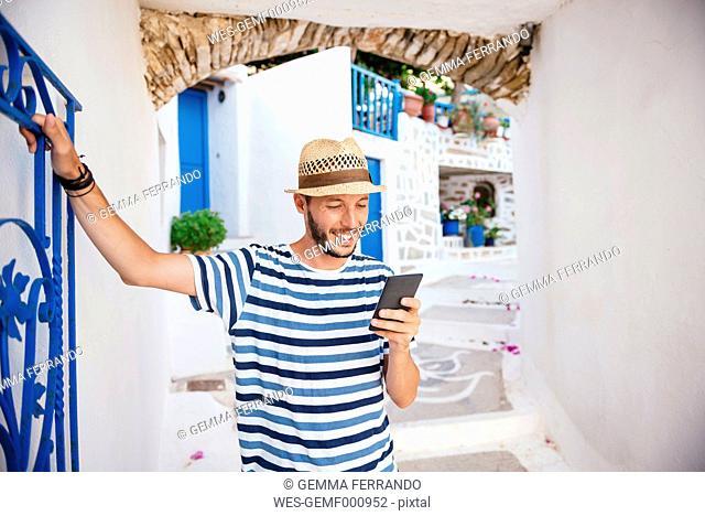 Greece, Amorgos island, young man using a smartphone