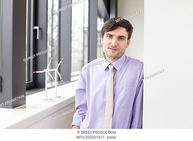Portrait of businessman leaning on wall, smiling