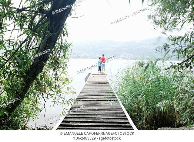 Children fishing on a pier at Lake Maggiore, Ranco, Italy