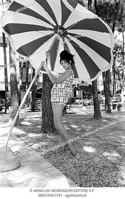 Italian actress Stefania Sandrelli posing leaning against a beach umbrella somewhere in Versilia. Italy, 1960