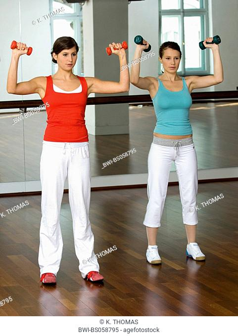 young women in fitness studio training with dumb-bell, Austria