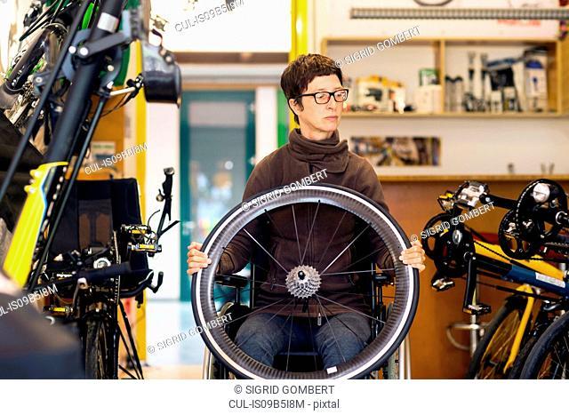Woman in wheelchair in bicycle repair shop, holding bicycle wheel