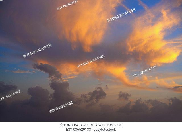 Sunset sky with orange golden clouds on blue background