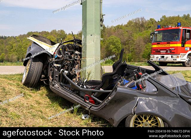 18 April 2020, Bavaria, Derching: A power pole sticks out of a Porsche after the latter has gone off the road in a slight right-hand bend and crashed into the...