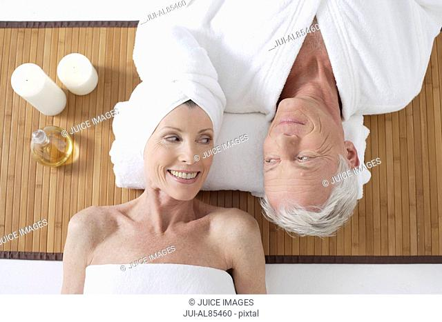 High angle view of senior couple laying on floor with candles and aromatherapy oil
