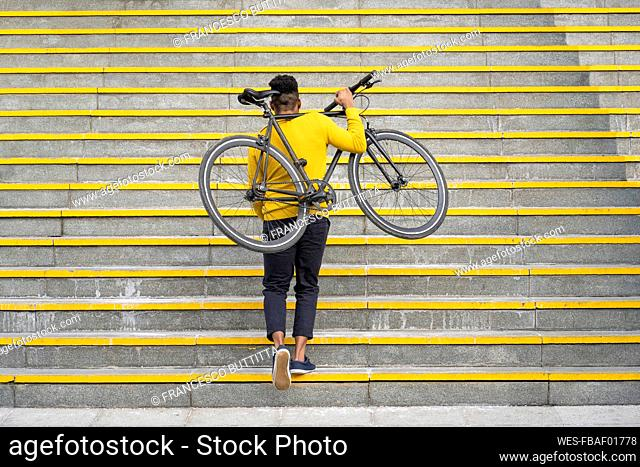 Young man carrying bicycle while climbing on staircase