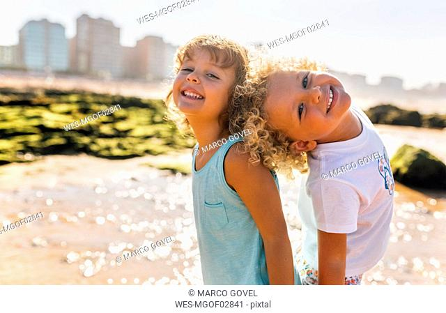 Portrait of happy little boy and girl standing bback to back on the beach