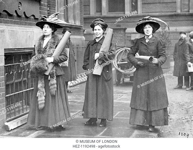 Three suffragettes prepare to chain themselves to the railings, 1909. Vera Holme, the WSPU chauffeur, is on the right. Padlocking themselves to the railings of...