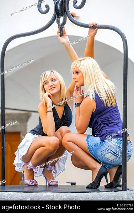 Two teen-girls are posing squatting on a water-well