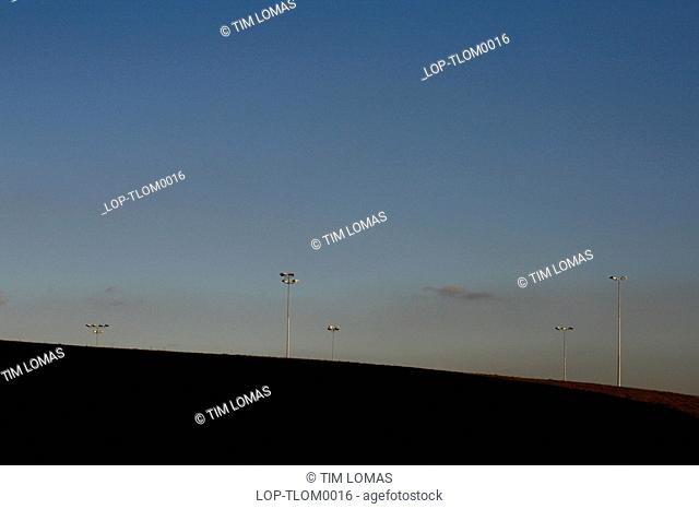 Floodlights on a hill at twilight. Newcastle started life as a Roman fort Pons Aelius along Hadrian's Wall, the border between Roman controlled Britain and the...