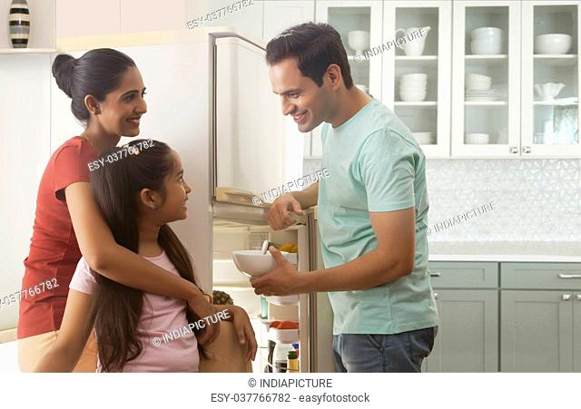 Family eating in front of open refrigerator